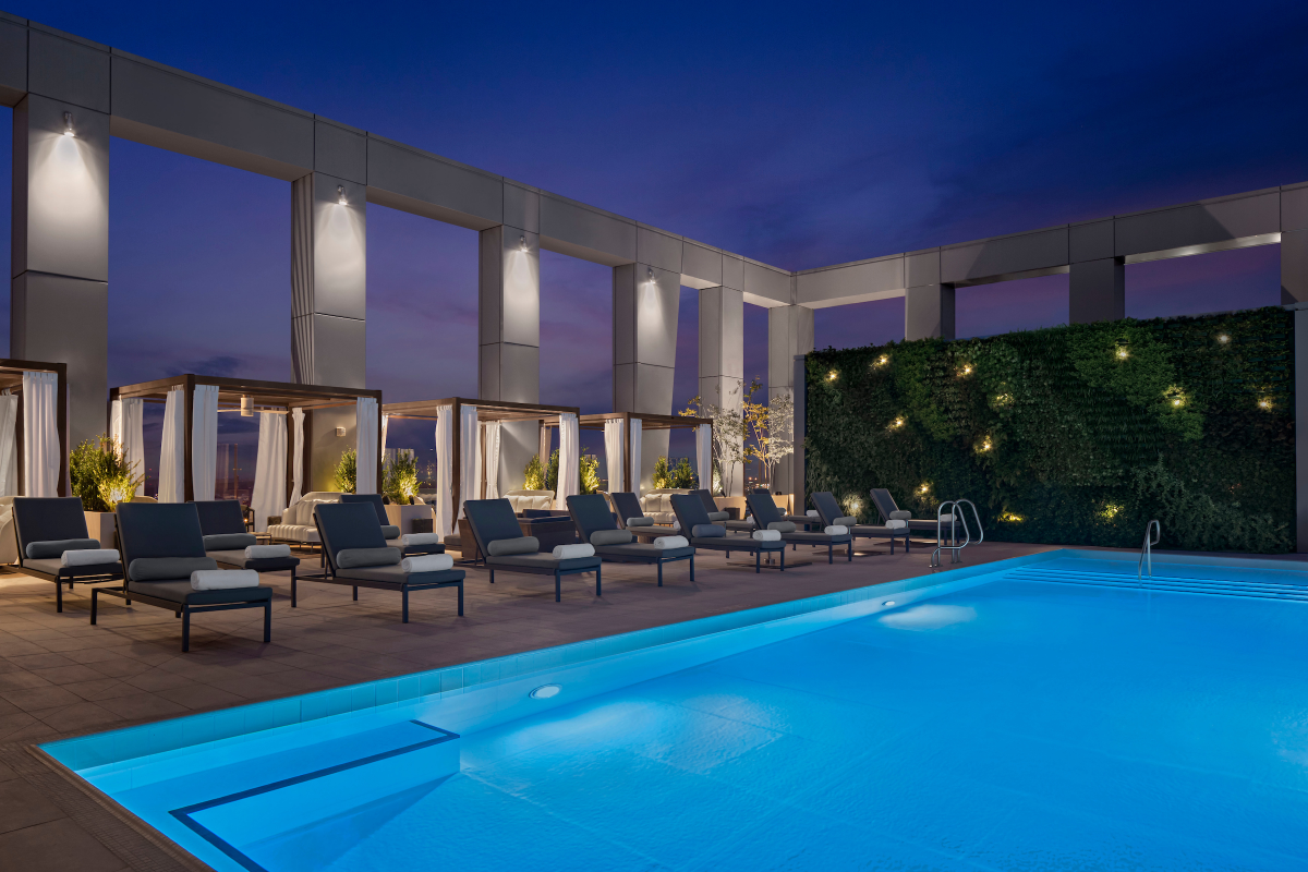 The pool and outdoor sitting area at night at The Joseph hotel.